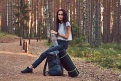 A menina do moderno do turista guarda uma garrafa da água, parada para descansar em uma floresta bonita do outono foto de stock royalty free