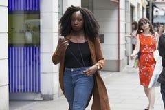 a menina do moderno vestiu-se no estilo fresco do londrino que anda na pista do tijolo, uma rua popular entre povos na moda novos Fotografia de Stock Royalty Free