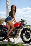 Menina do motociclista em um casaco de cabedal em uma motocicleta fotos de stock