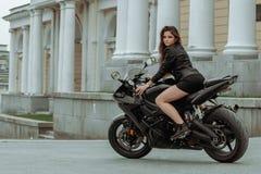 A menina do motociclista monta uma motocicleta na chuva Primeira pessoa vista fotos de stock royalty free