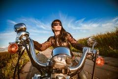 Menina do motociclista que senta-se na motocicleta foto de stock