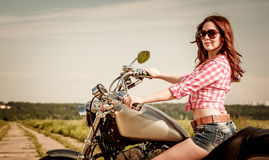Menina do motociclista que senta-se na motocicleta Fotos de Stock Royalty Free