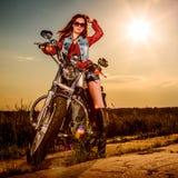 Menina do motociclista que senta-se na motocicleta Fotografia de Stock