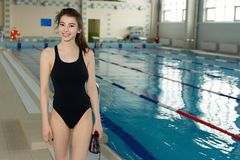 Menina do nadador no roupa de banho preto que sorri na piscina imagens de stock royalty free