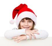 Menina do Natal com o chapéu de Santa atrás da placa branca que olha a câmera Isolado no branco Foto de Stock