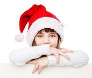 Menina do Natal com o chapéu de Santa atrás da placa branca que olha a câmera Isolado no branco Fotografia de Stock