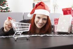 Menina do Natal com o mini carro do trole da compra Fotografia de Stock