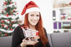 Menina do Natal com o mini carro do trole da compra Fotografia de Stock Royalty Free