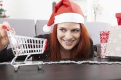 Menina do Natal com o mini carro do trole da compra Imagens de Stock Royalty Free