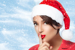Menina do Natal em Santa Hat que faz um sinal do silêncio Natal da forma Fotos de Stock Royalty Free