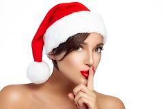 Menina do Natal feliz em Santa Hat que faz um sinal do silêncio Fotos de Stock