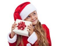 Menina do Natal feliz que verifica o presente Fotos de Stock Royalty Free