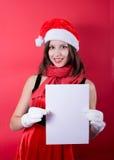 Menina do Natal no chapéu de Santa que guarda a bandeira. Imagem de Stock Royalty Free
