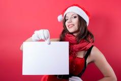 Menina do Natal no chapéu de Santa que guarda a bandeira. Fotos de Stock Royalty Free