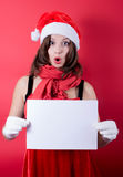 Menina do Natal no chapéu de Santa que guarda a bandeira. Fotografia de Stock