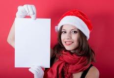 Menina do Natal no chapéu de Santa que guarda a bandeira. Fotografia de Stock Royalty Free
