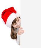 Menina do Natal no chapéu do ajudante de Santa com placa branca vazia isola Foto de Stock Royalty Free