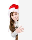 Menina do Natal no chapéu do ajudante de Santa com placa branca vazia isola Imagem de Stock