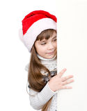 Menina do Natal no chapéu do ajudante de Santa com placa branca vazia Isolado Fotografia de Stock Royalty Free