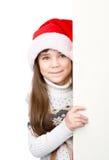 Menina do Natal no chapéu do ajudante de Santa com placa branca vazia Isolado Imagem de Stock Royalty Free
