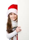 Menina do Natal no chapéu do ajudante de Santa com placa branca vazia no branco Fotos de Stock Royalty Free