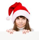 Menina do Natal no chapéu do ajudante de Santa que olha da placa vazia de trás e que olha acima Isolado no fundo branco Imagem de Stock Royalty Free