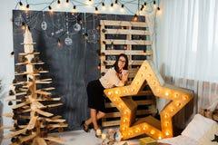 Menina do Natal no interior com velas e luzes imagens de stock royalty free