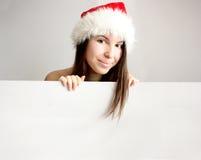 Menina do Natal que esconde atrás de uma placa em branco Fotografia de Stock