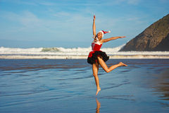 Menina do Natal que salta na praia fotos de stock
