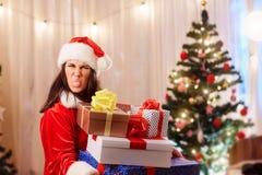 A menina do Natal que veste Santa Claus com os presentes em suas mãos mostra Fotografia de Stock