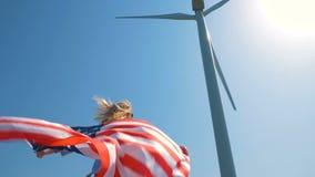 Menina do nativo americano com uma bandeira perto de um moinho de vento gigante em um campo no movimento lento vídeos de arquivo