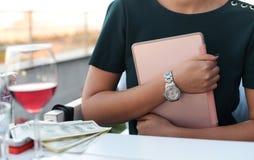 Menina do negócio com uma tabuleta nas mãos que sentam-se em uma tabela em um res fotos de stock royalty free