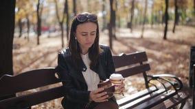 Menina do negócio em um banco de parque que come um croissant e que bebe o café de um copo de papel video estoque
