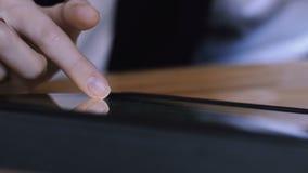 A menina do negócio lança através de um álbum de fotografias em uma tabuleta A mão do ` s do estudante desliza no ` s da tabuleta filme
