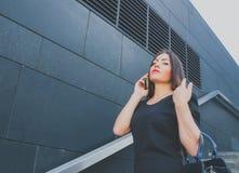 Menina do negócio na fala preta no telefone imagens de stock royalty free