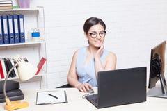 A menina do negócio senta-se em um escritório atrás de uma mesa com um computador Foto de Stock