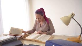 A menina do negócio senta-se no escritório para dobradores dos livros do secretário de papel filme