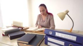 A menina do negócio senta-se no escritório para dobradores dos livros do secretário de papel video estoque