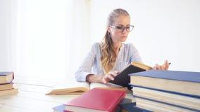 A menina do negócio senta-se nos dobradores que do papel do escritório o secretário lê livros video estoque