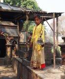 Menina do Nepali que joga o sino no templo hindu Fotos de Stock