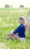 Menina do país perto de um monte de feno Gramado verde foto de stock
