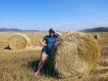 Menina do país que levanta no campo do feno foto de stock royalty free