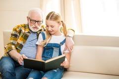 Menina do Preteen com o homem superior no livro de leitura dos monóculos junto imagem de stock