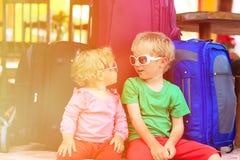 Menina do rapaz pequeno e da criança que senta-se em malas de viagem Fotografia de Stock Royalty Free