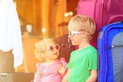 Menina do rapaz pequeno e da criança que senta-se em malas de viagem Fotos de Stock