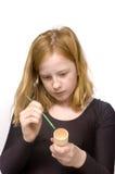 A menina do Redhead está pintando um suporte do ovo foto de stock royalty free