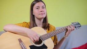 A menina do retrato aprende jogar a guitarra vídeos de arquivo