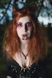 Menina do retrato com cabelo vermelho e vampiro ensanguentado da cara, assassino, psicótico, tema do Dia das Bruxas, mulher ensan Foto de Stock Royalty Free