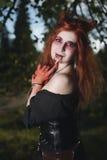 Menina do retrato com cabelo vermelho e vampiro ensanguentado da cara, assassino, psicótico, tema do Dia das Bruxas, mulher ensan Imagens de Stock