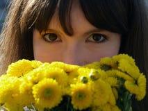 A menina do retrato com flores amarelas fecha-se acima fotografia de stock